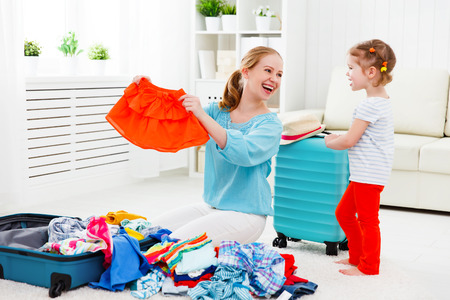 woman bag: happy family tourist mother and child daughter suitcases packed for vacation Stock Photo