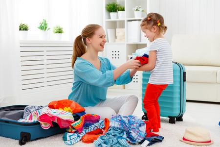 family vacation: happy family tourist mother and child daughter suitcases packed for vacation Stock Photo