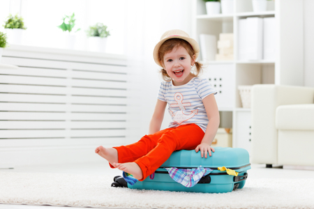 toddler: happy child girl tourist packs clothes into a suitcase for travel, vacation Stock Photo