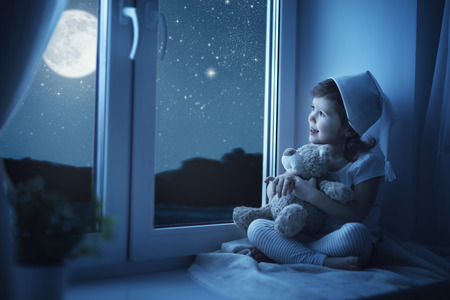 bedtime: child little girl at the window dreaming and admiring the starry sky at bedtime night