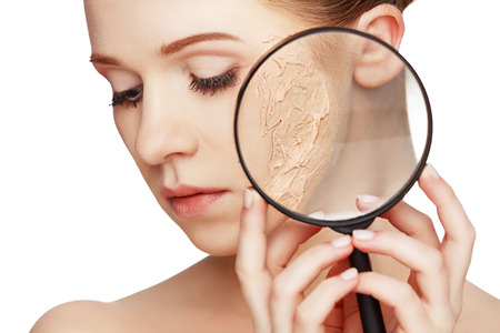 concept of rejuvenation and skin care. face of a beautiful girl with a problem skin and magnifier
