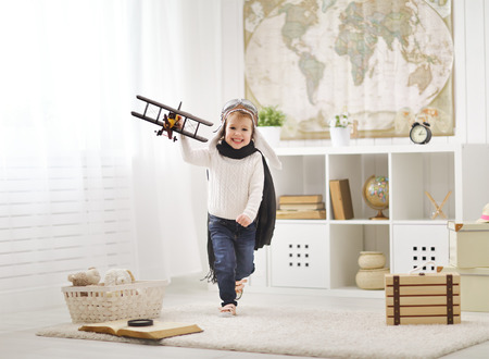 concept of children's dreams and travels. happy child playing with an airplane pilot and runs across the room