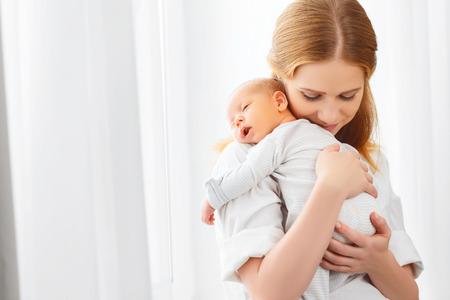 ni�o durmiendo: beb� reci�n nacido en un tierno abrazo de la madre en la ventana Foto de archivo