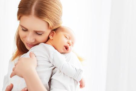 Bébé nouveau-né dans une tendre étreinte de la mère à la fenêtre Banque d'images - 55011056