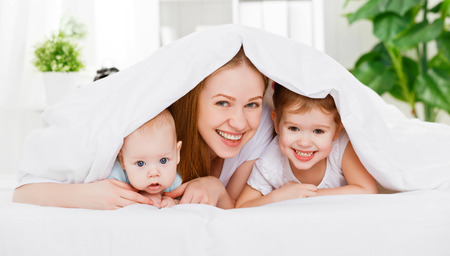 happy family mother and two children, son and daughter in bed playing  under  blanket