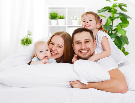 happy family mother, father and two children at home in bed Foto de archivo
