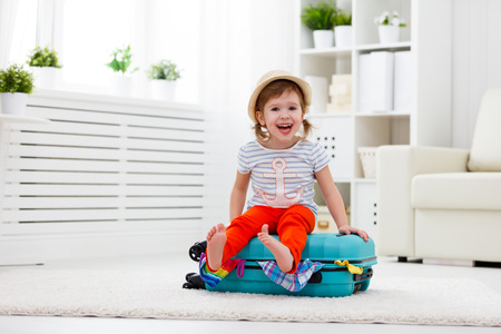 Gelukkig kindmeisje toerist pakt kleding in een koffer voor reizen, vakantie