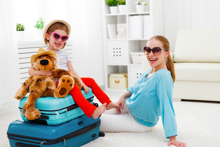 happy family tourist mother and child daughter suitcases packed for vacation Stock Photo