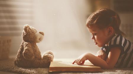 kind klein meisje het lezen van een magisch boek in het donker naar huis met een speeltje teddybeer