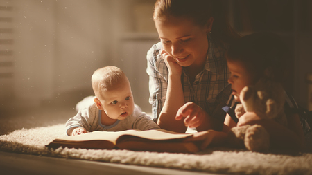 happy family mother and children read a book in the evening at home