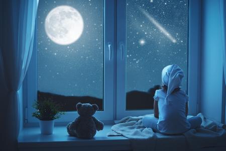imaginacion: niña niño en la ventana soñando y admirar el cielo estrellado de la noche antes de acostarse Foto de archivo