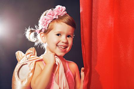 little child girl ballerina ballet dancer on the stage in red side scenes