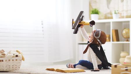 concept van de kinderen dromen en reizen. piloot vlieger kind met een speelgoed vliegtuig speelt thuis in zijn kamer