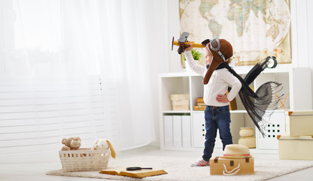 kid room: concept of childrens dreams and travels.  pilot aviator child with a toy airplane plays at home in his room