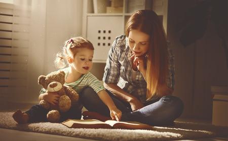 gelukkig gezin moeder en dochter een boek te lezen in de avond thuis