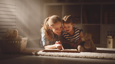 mère de famille heureuse et sa fille de lire un livre dans la soirée à la maison