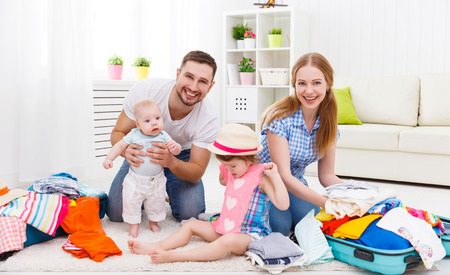 young people: happy family mother, father and two children packed suitcases for the trip holiday travel vacation Stock Photo