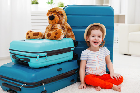travel bag: happy child girl collect the suitcase on vacation