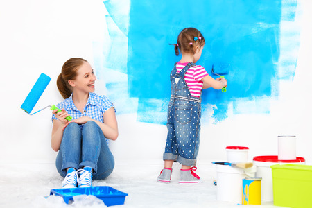 幸せな家族母と子娘修理、自宅の壁を塗る