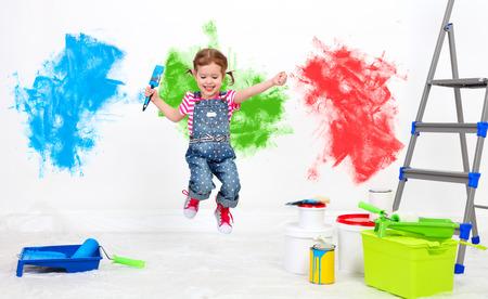 feliz chica divertida niño haciendo reparaciones, saltando y pintar la pared en el país