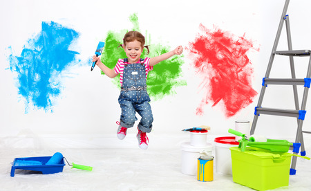 happy funny child girl doing repairs, jumping and paint the wall at home