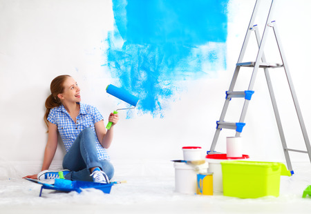 wall paint: happy woman doing repairs, paint the wall at home