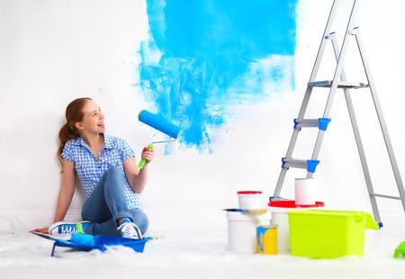 修理をして幸せな女、自宅の壁を塗る