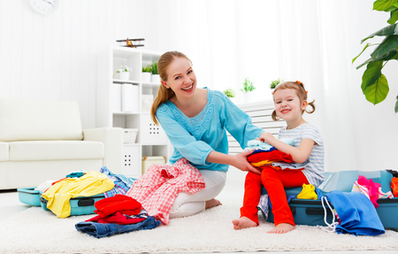happy mom: happy family tourist mother and child daughter suitcases packed for vacation Stock Photo