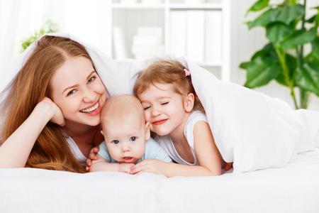 cama: madre de familia feliz y dos hijos, hijo e hija en la cama jugando bajo la manta