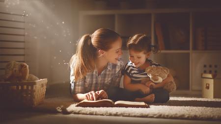 anochecer: madre de familia feliz y la hija leyeron un libro en la tarde en casa Foto de archivo