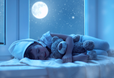 child little girl sleeping at the window dreaming and admiring the starry sky at bedtime night