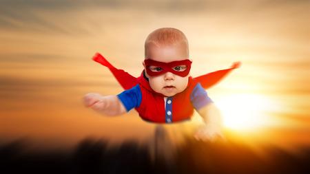 Kleinkind kleines Baby Übermensch Superhelden mit einem roten Umhang durch den Himmel fliegen