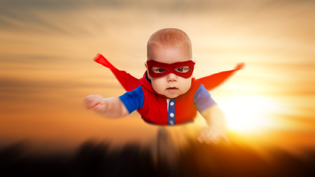 toddler little baby superman superhero with a red cape flying through the sky
