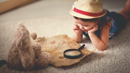 soñando: el concepto de viaje. niña hijo en casa soñando con los viajes y el turismo, la exploración del mapa del mundo y el globo