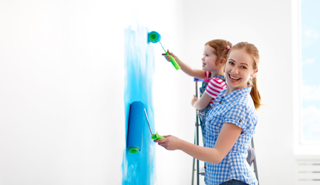 work from home: happy family mother and child daughter making repairs, paint the wall at home