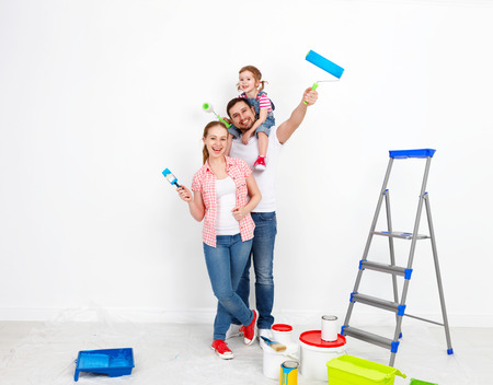 happy family mother father and baby daughter are doing repairs paint wall at home