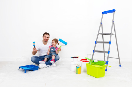 happy family father and child daughter making repairs, paint the wall at home