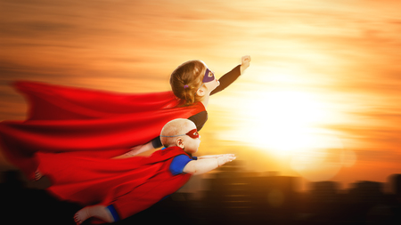 children superheroes flying across sunset sky. boy and girl brother and sister Stock Photo