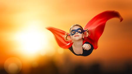 La muchacha del niño superhéroe volando por el cielo al atardecer