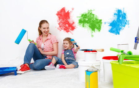 painter girl: happy family mother and child daughter making repairs, paint the wall at home
