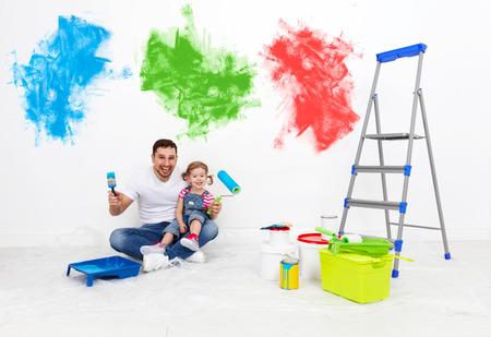Feliz padre de familia y su hija niño se hacen reparaciones, pintura de la pared en el país Foto de archivo - 55011134