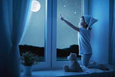 창에서 아이 어린 소녀 꿈과 취침 밤에 별이 빛나는 하늘을 감상
