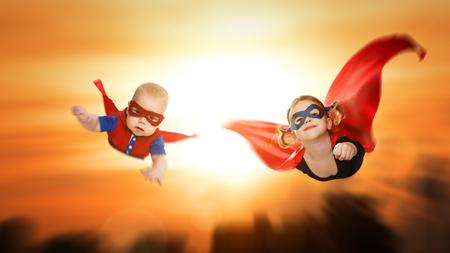 夕焼け空を横切って飛んで子供のスーパー ヒーロー。男の子と女の子の兄と妹