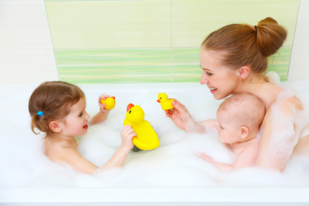 bathing in a bath with foam mother together children baby