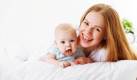 glückliche Familie Mutter mit neugeborenen Baby im Bett Lizenzfreie Bilder