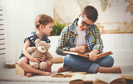 man studying: children brother and sister, boy and girl reading a book at home Stock Photo