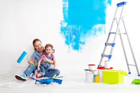 gelukkig gezin moeder en kind dochter maken van reparaties, verf de muur thuis