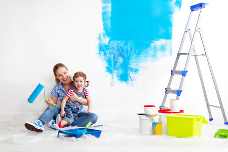 Madre e hija familia feliz niño que hace reparaciones, pintura de la pared en el país Foto de archivo - 55645289