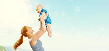 glückliche Familie Mutter und Baby Sohn spielen und Spaß am Strand am Meer im Sommer mit