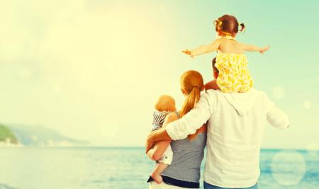glückliche Familie von Vater, Mutter und zwei Kinder, Baby-Sohn und Tochter am Strand bei Sonnenuntergang Standard-Bild